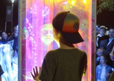 Child looking into illuminated rainbow mirror at night