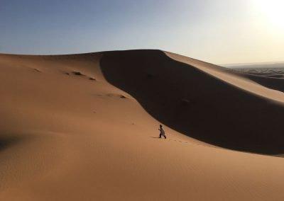 Small figure climbs a sand dune against a bright blue sky