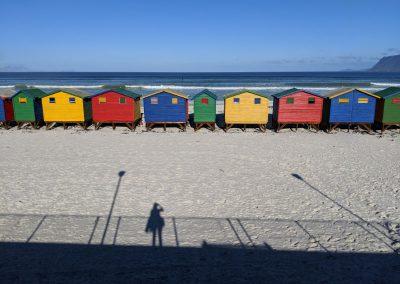 Blue, green, red beach houses on a white sand beach