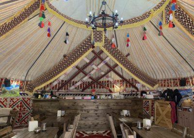 Wooden tables inside a yurt restaurant
