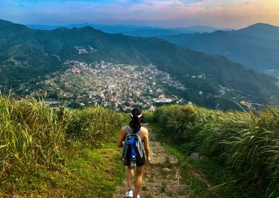 A hiker travels down a mountain path to a city
