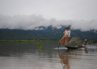 Man steering his boat with a pole against a background of clouds and mountains