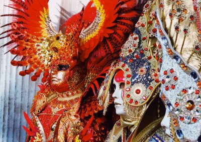 Two festival-goers in elaborate red and jeweled costumes